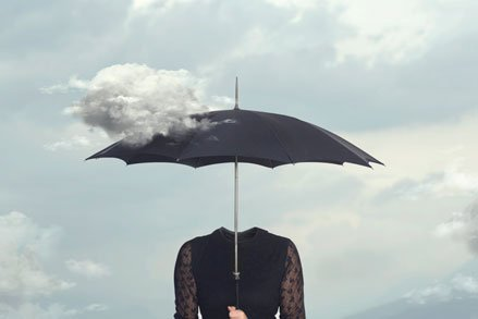headless woman hiolding umbrella in partly cloudy sky