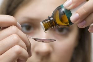woman dripping homeopathic tincture into spoon