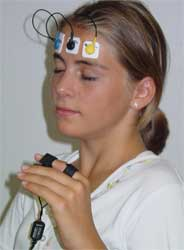 Young woman with biofeedback monitors on her forhead and index finger.